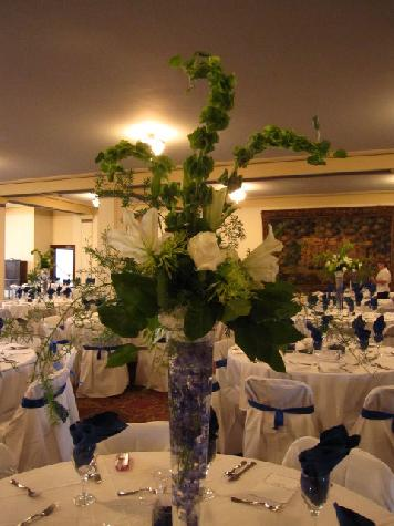White lilies, white roses, green spider mum, bells or Ireland, and blue delphinium. Wedding at Scottish Rite.
